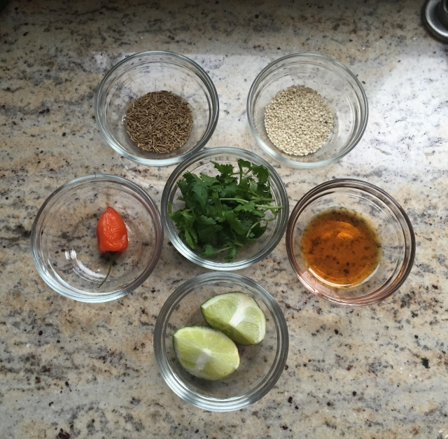 Figure 1: Left to right: hot red pepper, cumin seeds, sesame seeds. sesame oil. © 2015 Sangeeta Pradhan, lime wedges and cilantro in the center.