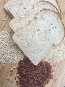 From bottom center, clockwise: red rice, barley, whole grain bread, and brown rice.