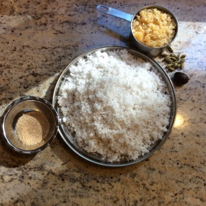 Clockwise,toasted poppy seeds, crushed jaggery, whole cardamom, nutmeg and fresh coconut. ©